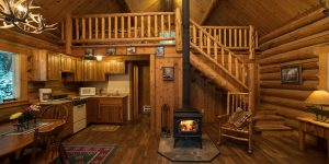 Western Pleasure Guest Ranch Hunter Cabin interior photo with wood fire burning, log railings and wood floor