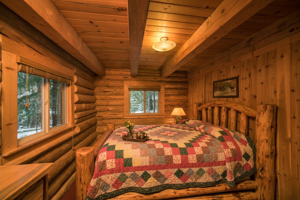 Pacific Northwest cabin rental private bedroom log walls and log bed with quilt
