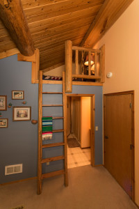 ranch lodge room with ladder into small loft and door into bathroom
