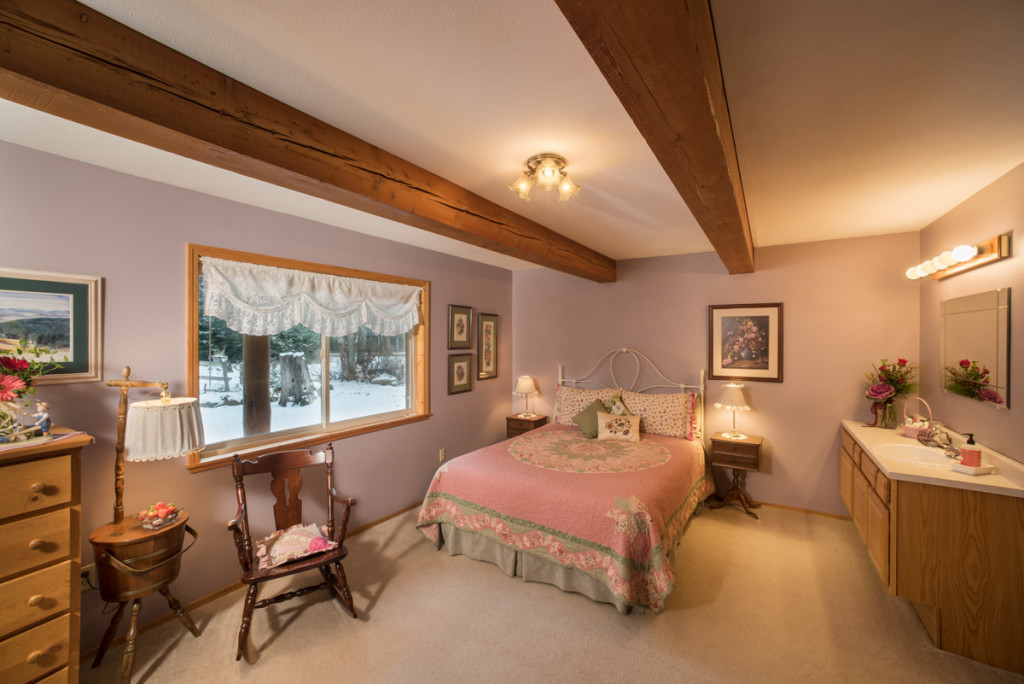 Guest room with quilted bed, rocking chair, bathroom vanity, and snow outside window