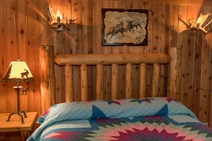log bed with quilt in wood panel room with antler lights on the wall
