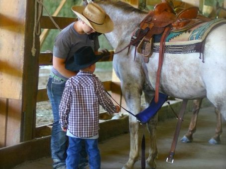 child-saddling-horse