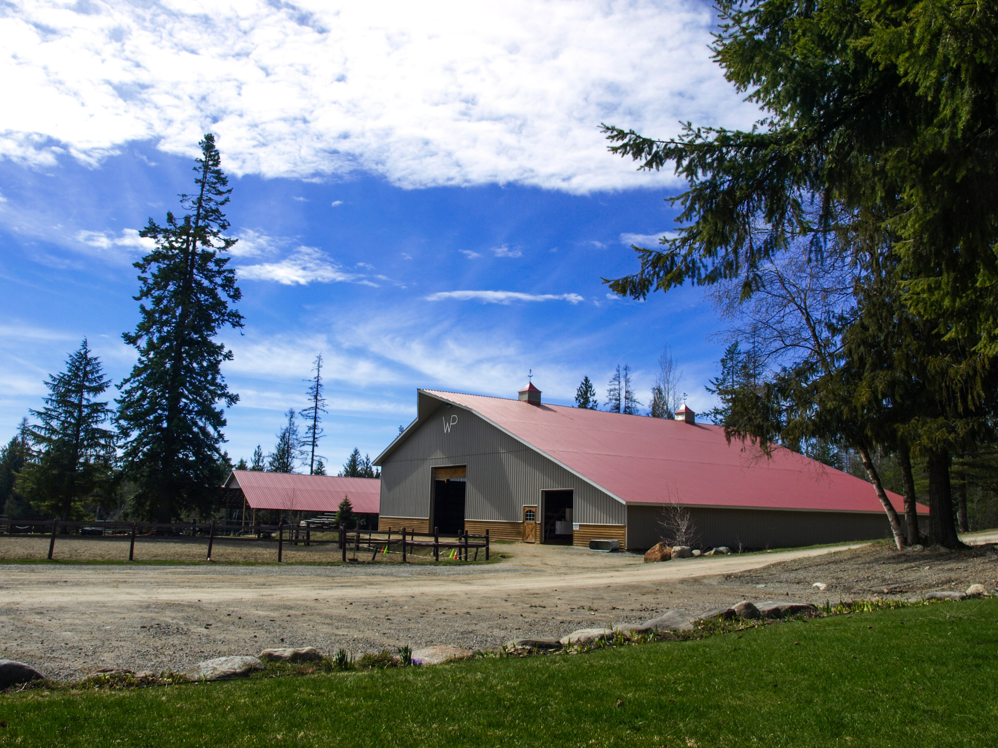 Large barn with red roof and blue sky above