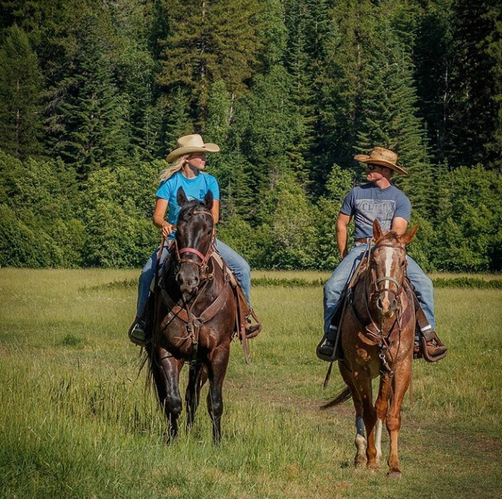 Cowboy and Cowgirl riding in a field looking at each other