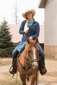 Cowgirl wearing glasses and holding a clipboard smiling and riding a dun Quarter Horse Mare