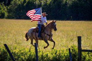 Cowboy running an Appaloosa Gelding through a green field while holding a waving American flag