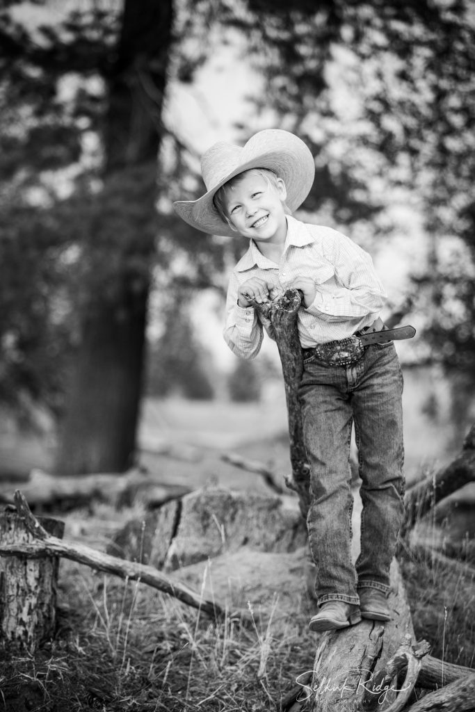 Little boy in cowboy hat leaning on a stick and smiling