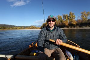 Man smiling in a boat while rowing down the Kootenai River