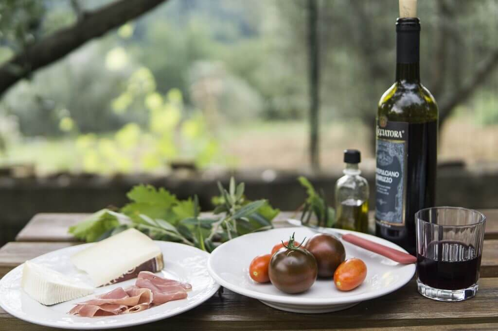 Picnic dinner of meat, cheese, vegetables and wine