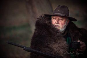 Mountain man in buffalo rug with gun