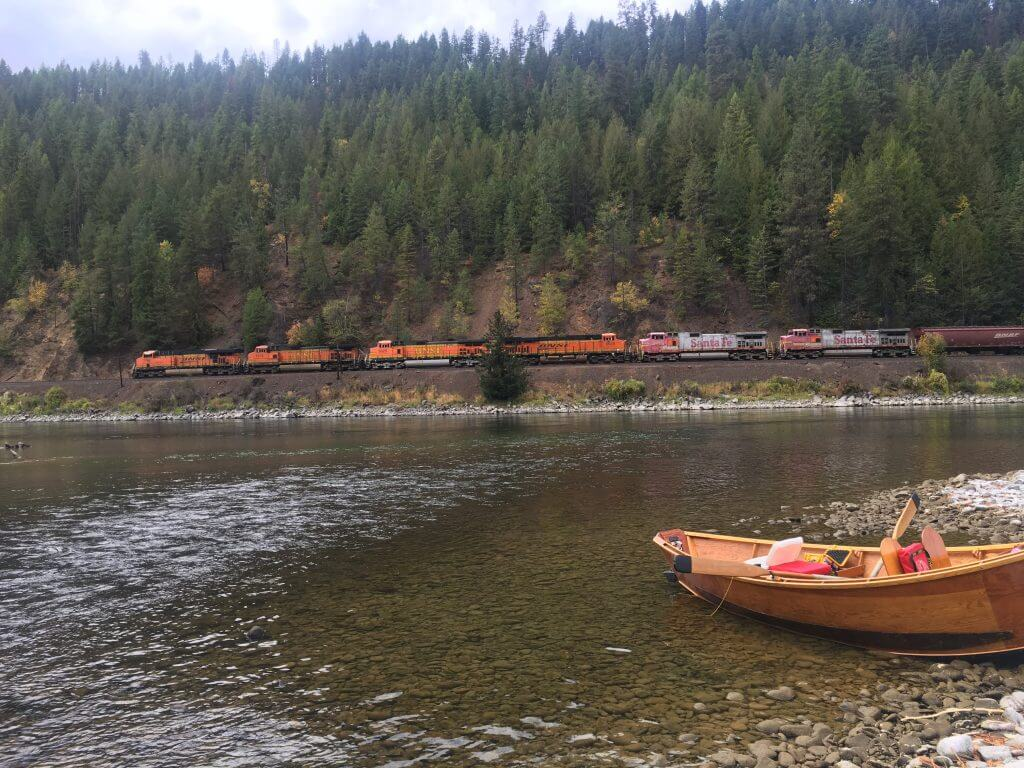 Long Drift Outfitters Fly Fishing Kootenai River boat in the river next to a train