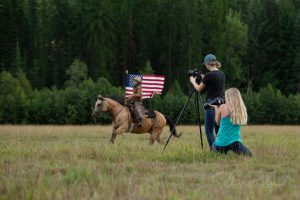 Boy riding with American Flag with two photographers taking photos