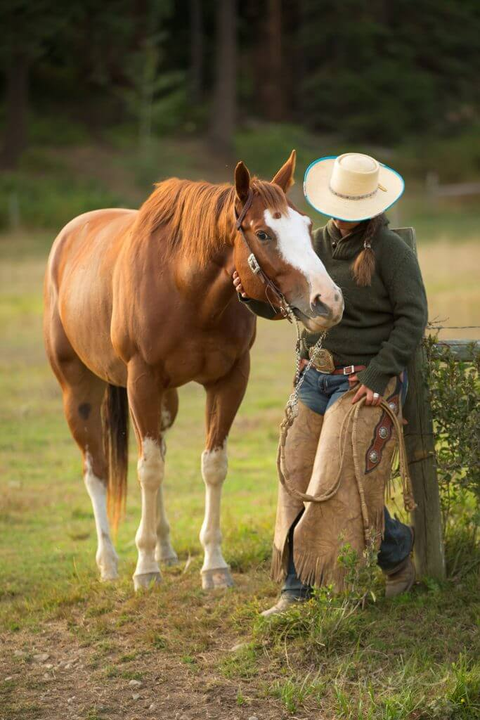 Cowgirl with sorrel horse by a fence