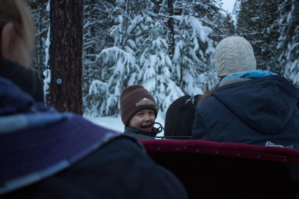 little boy in a hat smiling while riding on a sleigh through the snow covered forest