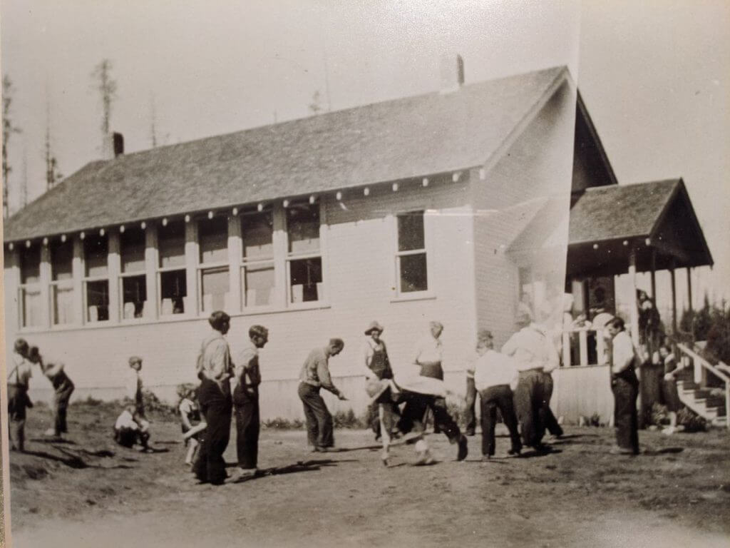 Old black and white photo of children playing in front of a large white school house with lots of windows along the side