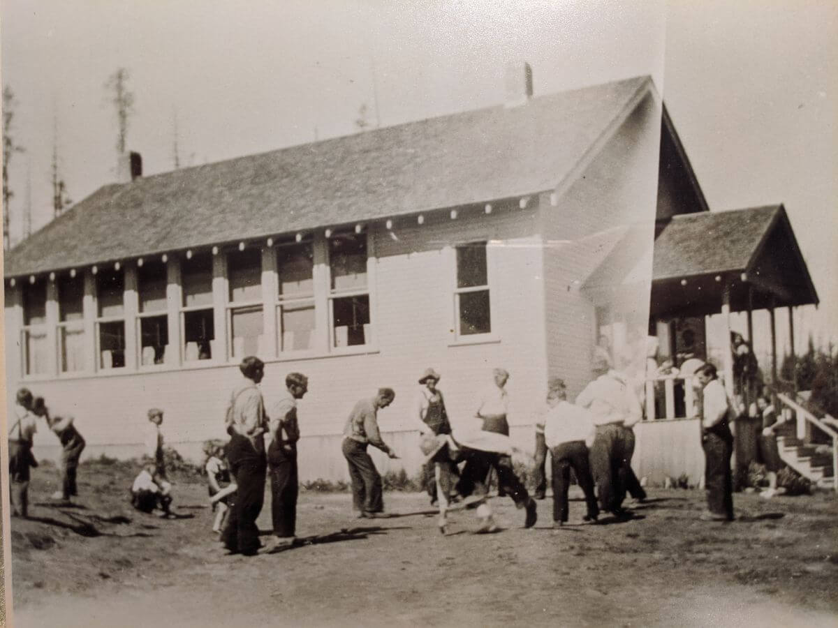 Old black and white photo of children playing outside of a large white school house with many windows along the side