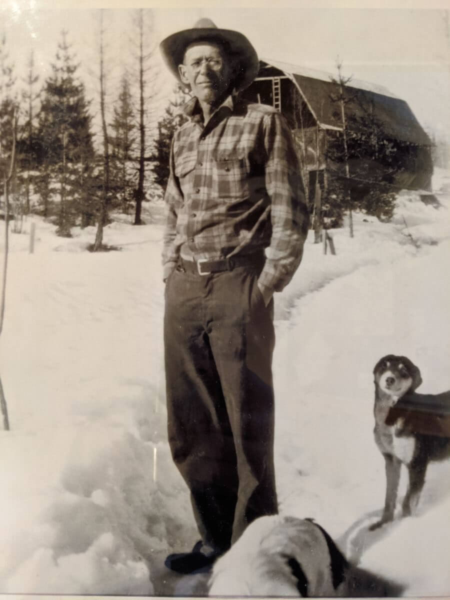 Black and white photo of a man standing in the snow with a dog next to him