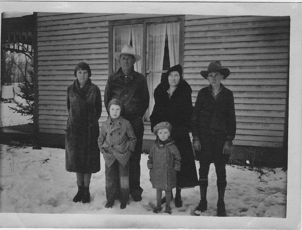 Old black and white historical photo of husband, wife and 4 kids standing with coats and hats on outside of a house in the snow