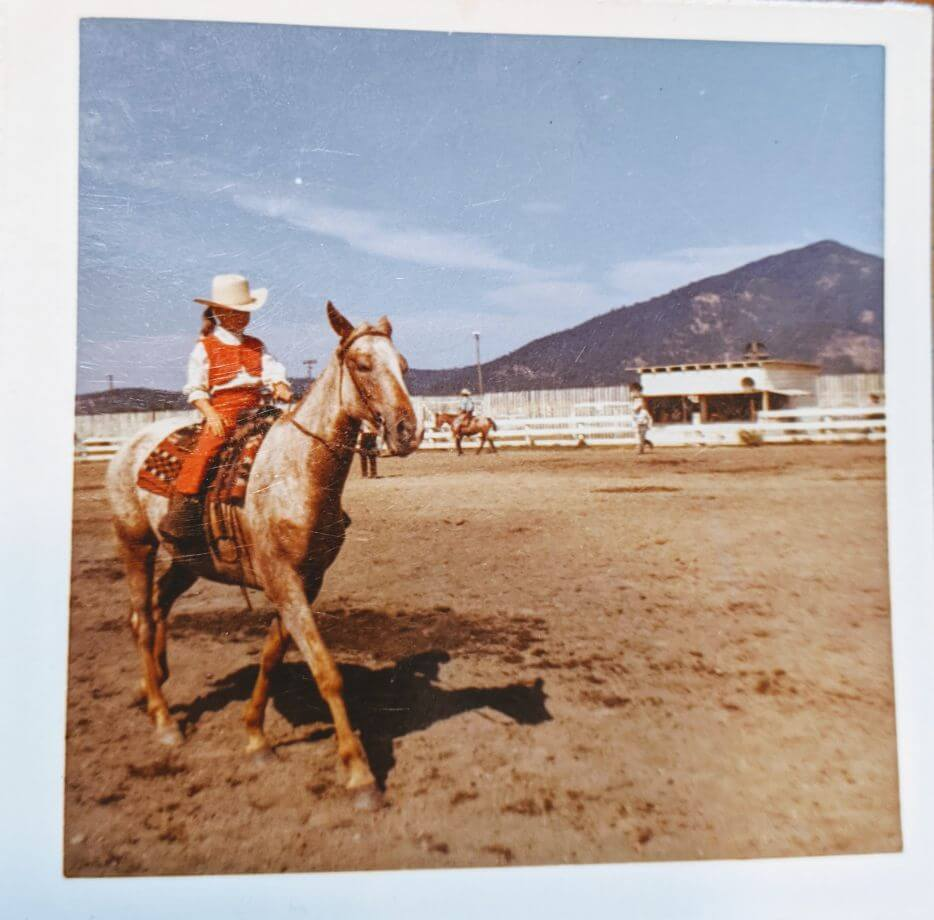 Vintage photo of little girl in red riding an Appaloosa in an arena