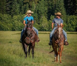 Cody and Emma riding horses across the pasture