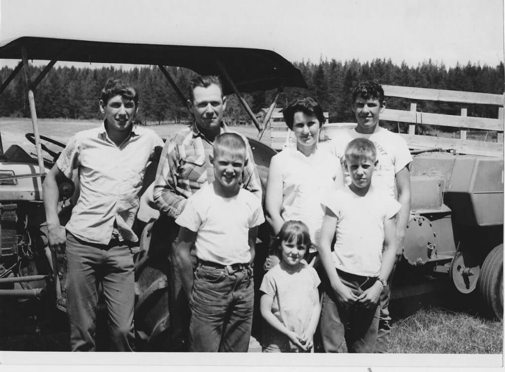 black and white photo of a family in jeans and white shirts standing in front of an old tractor in a hay field