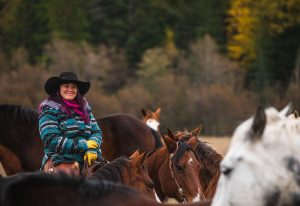Cowgirl smiling and sitting on ranch horse in a field of horses and fall colors