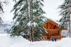 log cabin in the snow with children in front pulling sleds