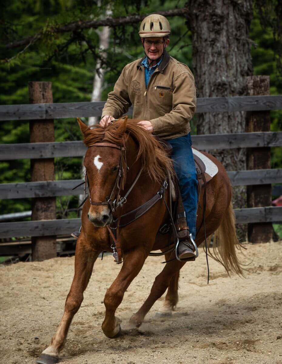 cowboy riding sorrel horse in arena at Idaho's Western Pleasure Guest Ranch
