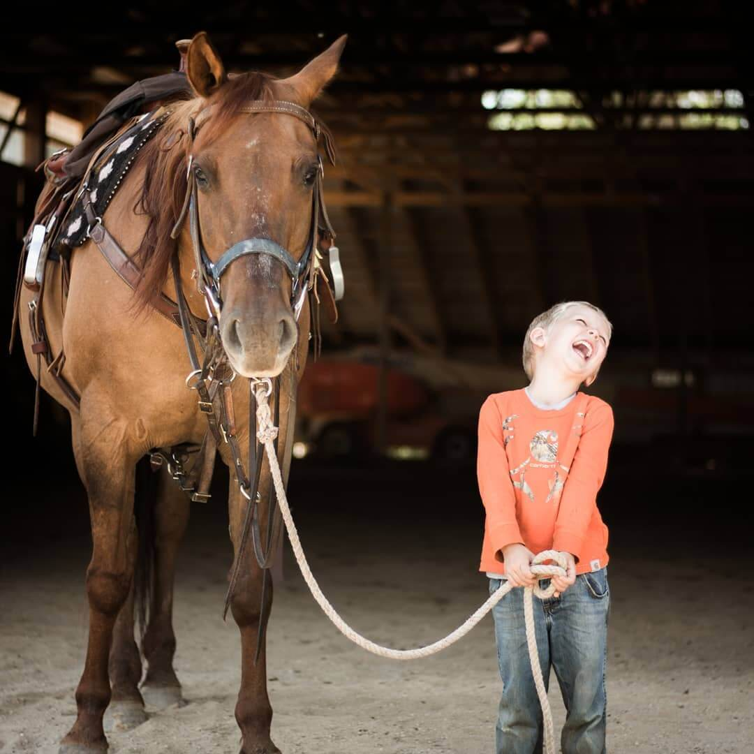 Little boy laughing while holding horse's lead rope