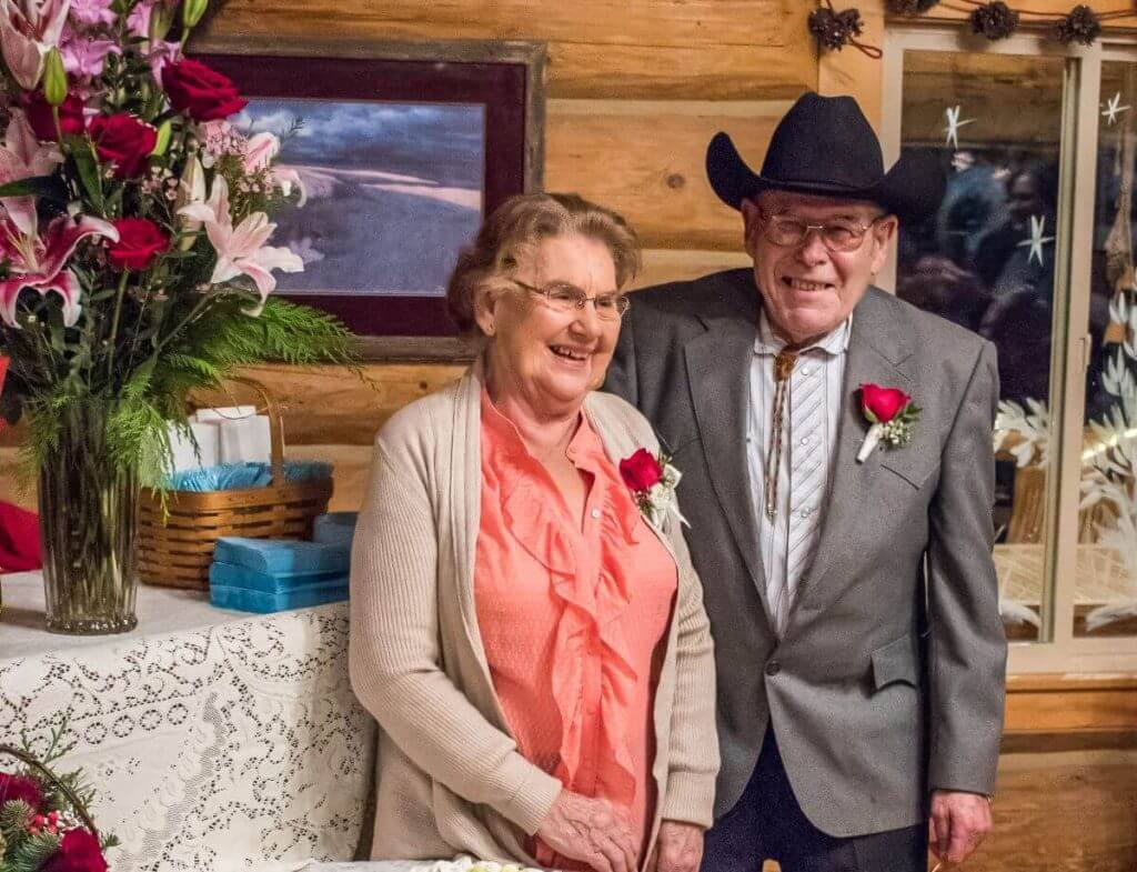 Elderly couple standing next to each other and laughing inside a log lodge as they celebrate their anniversary and their ranch legacy.
