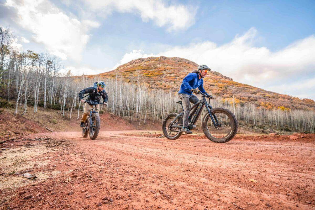 two men riding ebikes on a red dirt road