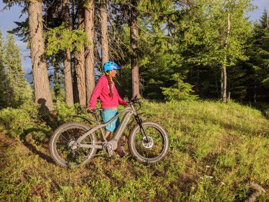 woman standing next to black QuietKat ebike in a green forest