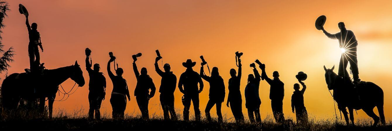 silhouette of people holding up cameras and two people standing on horses holding up cowboy hats