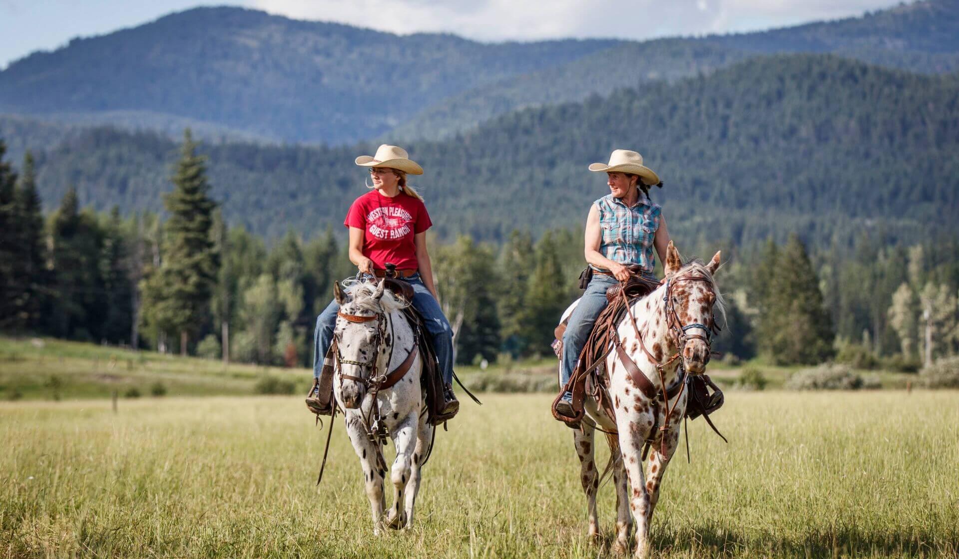 two women ride leopard Appaloosa horses across a green field